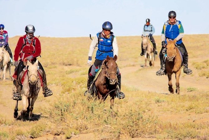 Horses and riders engaged in Gobi Desert Cup.