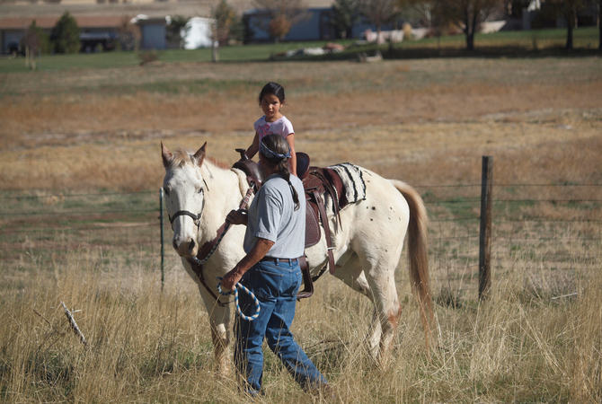 Encouraging a young girl to enjoy riding a white appaloosa horse.