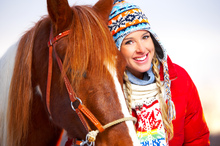 Warmly-clad girl enjoying time with her horse.
