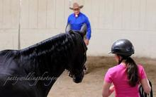 Monty Roberts teaching horse training techniques to girl.