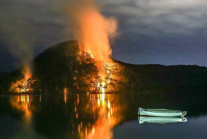 Wild fire on mountain side near bay in Australia