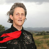 Temple Grandin in a country setting with the wind blowing her hair and scarf.