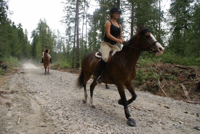 Women riding horses in Cavallo boots on the rocky trail.