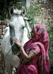 Woman with her white horse in India.