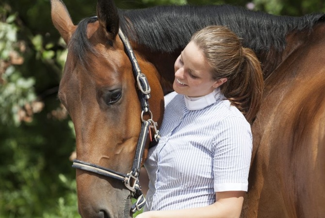 Girl using positive reinforcement while training horse.