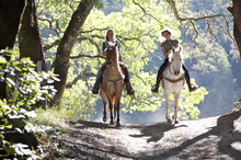 Two women enjoying a trail ride on their horses.