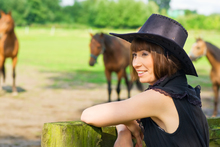 Woman observing horse in pasture.