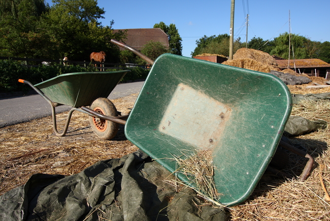 Keeping horse stalls mucked and clean with wheelbarrow and helpful tools.