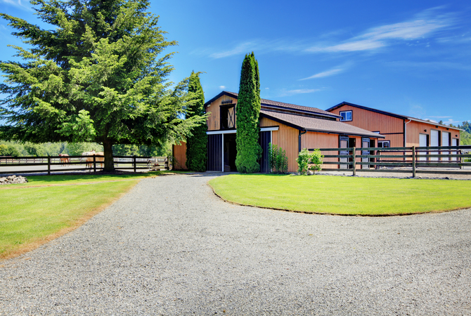 A modern barn that allows room for horses and plenty of storage.