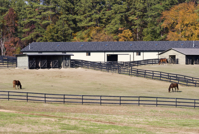 A wll-planned barn with corrals, paddock, pasture, and storage areas.