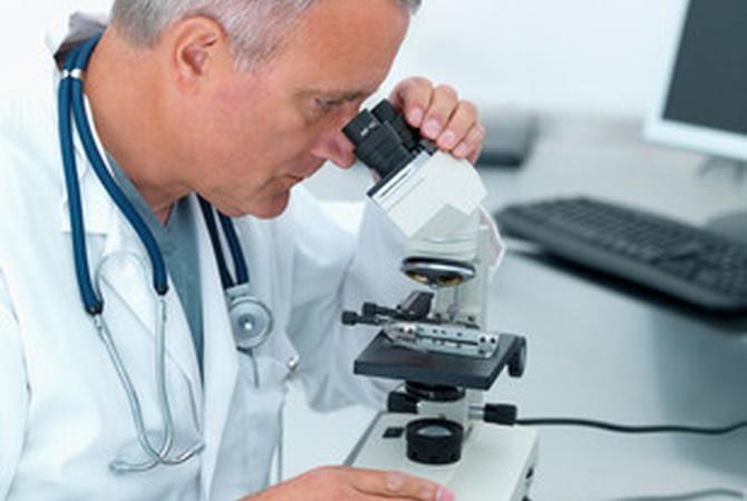 Veterinarian using microscope.