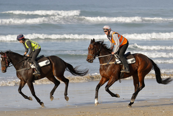 Wearing helmets while riding horses on the beach.