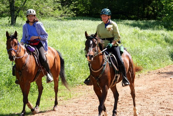 Horseback riders wearing appropriate helmets.