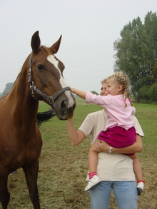 Woman and young girl petting a cooperative horse.