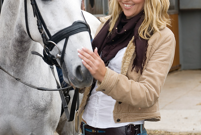 Woman getting horse ready for training by studying his reactions.