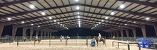 An indoor horse arena with LED lighting.
