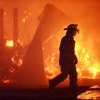 Fireman walking past a burning horse barn.