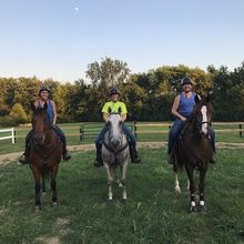 Three women wearing Troxel helmets while riding their horses.